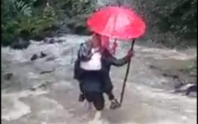 Astarada müəllim qızını çiynində çaydan keçirərək məktəbə aparır - Video